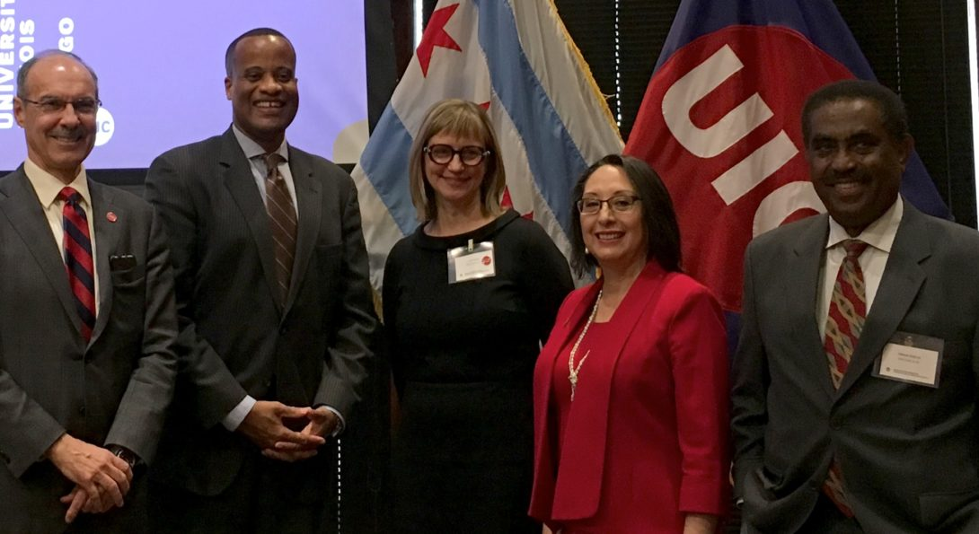 EDA University Center staff and visiting dignitaries stand in front of UIC flags